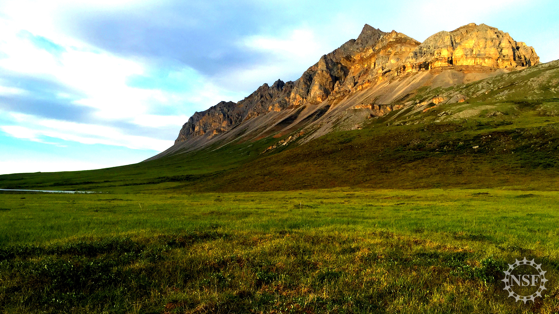 A rocky outcrop rises over the Alaskan tundra.