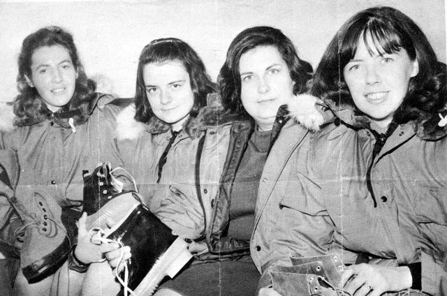 A black and white photo depicts four women in heavy coats sitting against a wall