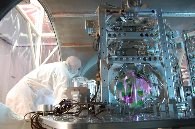 A worker in a white lab suit is pictured examining a large metal structure with wires