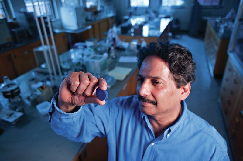 A man in a laboratory holds up a small blue disc between his fingers