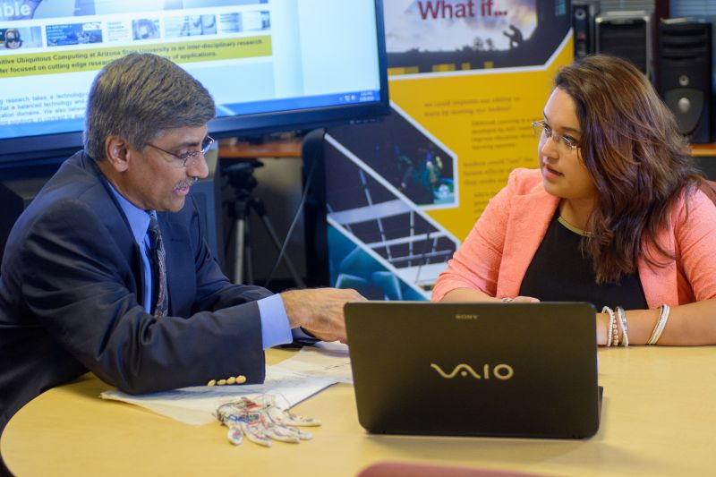 Dr. Panchanathan discusses a research project with a student while sitting at a table