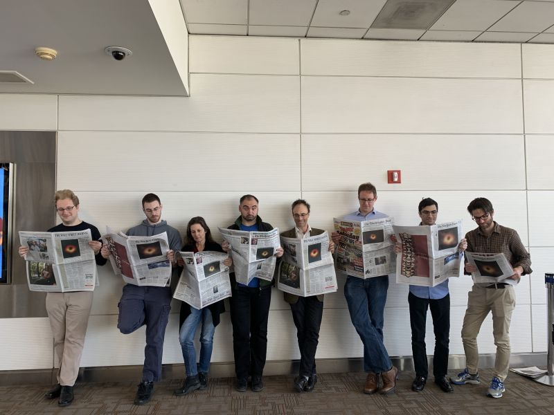 A group of people stand in a line each holding a news paper displaying the black hole image on the front page