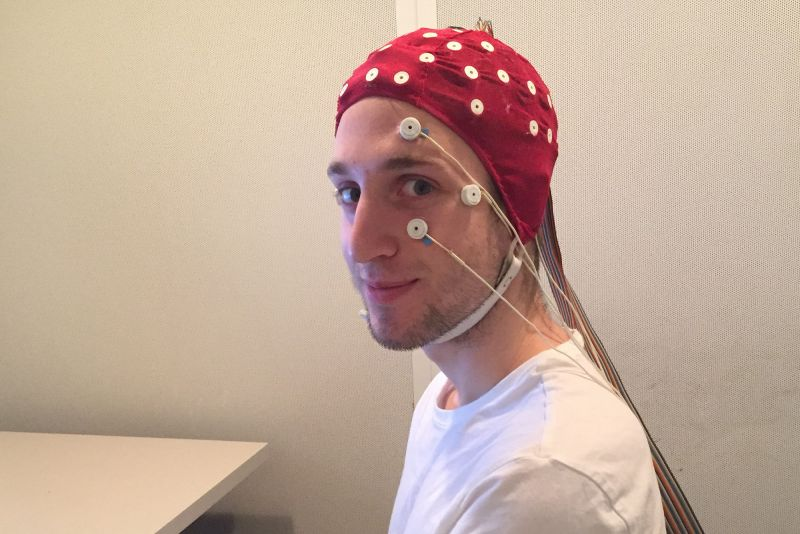 A man looks at the camera while wearing a red cap fitted with white electrodes