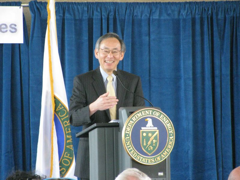 Steven Chu smiles while standing at a podium with a Department of Energy seal