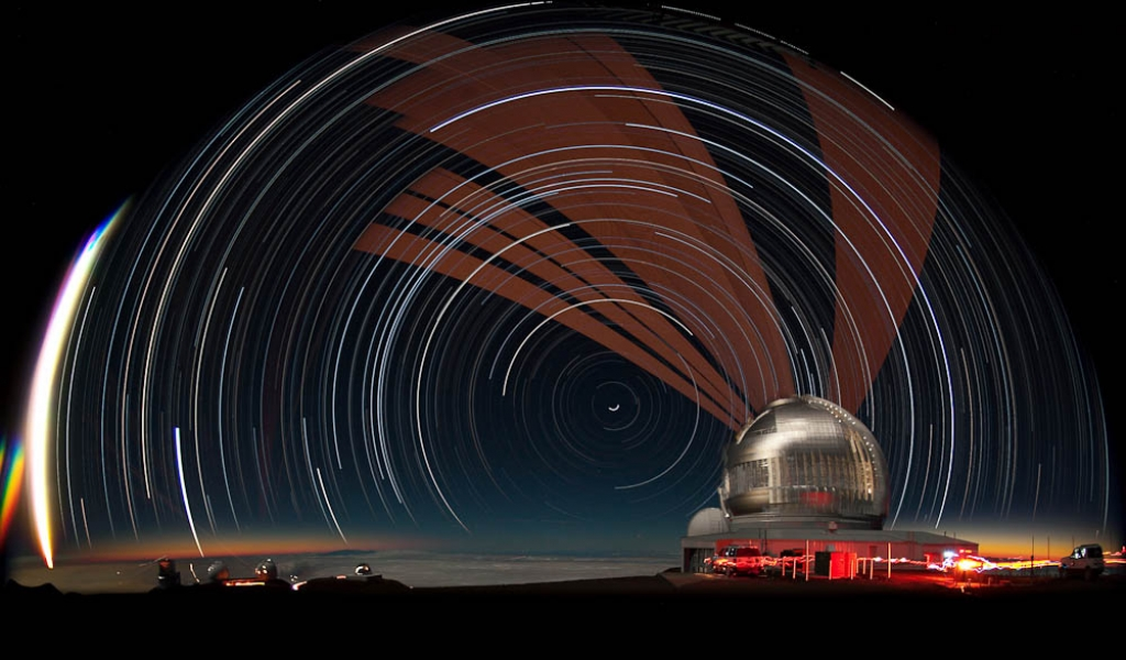 White and brown streams of light are seen in front of a night sky. To the right is a white domed building.