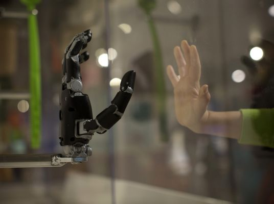 robot hand reaching out to touch a human hand